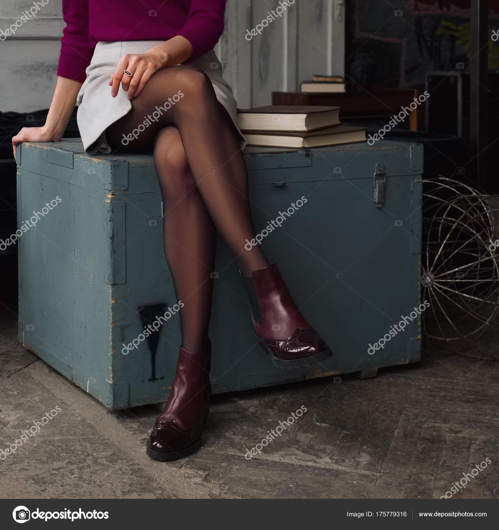 04d1581b8 Piernas mujeres en falda corta y medias negras sentada en caja de ...