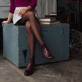 Photo Female legs in short skirt and black pantyhose sitting on wooden box near big books . Soft focus photo.