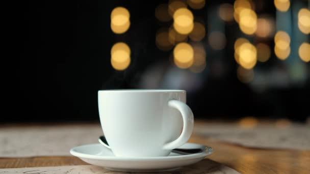 Bílý šálek kávy s párou na dřevěný stůl u okna