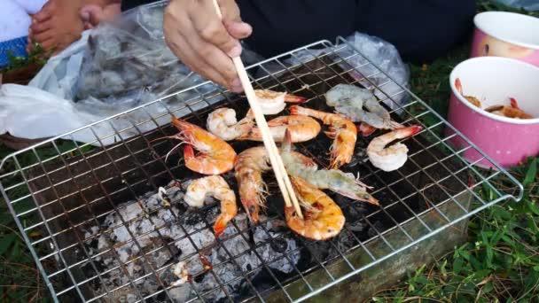 Ruce jsou grilované mořské plody Gril nebo gril s uhlím ve straně