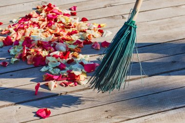Multicolored rose petals are swept with a broom after the weddin