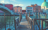 Old wooden pier and beautiful view on venetian chanal. Picturesque landscape. Architecture and landmarks. Venice is a popular tourist destination of Europe.