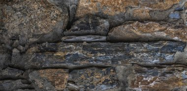 Blackened by time ancient stone wall Swiss Chalet. Natural stone wall (textured background).