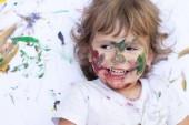 Malovaný vody barvy tvář dítěte. Legrační špinavé chlapeček na bílém pozadí
