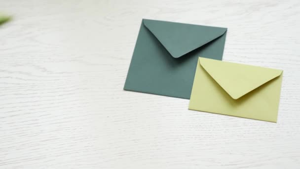 Woman hand put flower on envelops on wooden table background