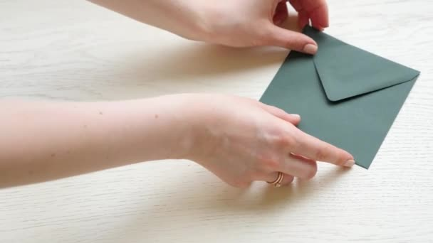 Woman hand put envelops and flower on wooden table background