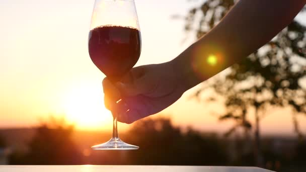 Rich red wine being poured into balloon wineglass