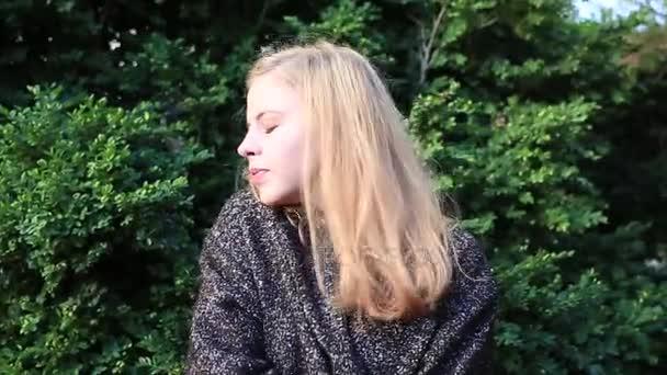 Mladá a hezká model pózuje pro kameru. Ona se směje, její vlasy vlající ve větru, tvářili se velmi šťastně