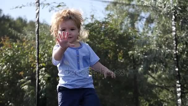 glückliches kleines blondes Kind mit braunen Augen springt zum ersten Mal und hat Spaß im Freien