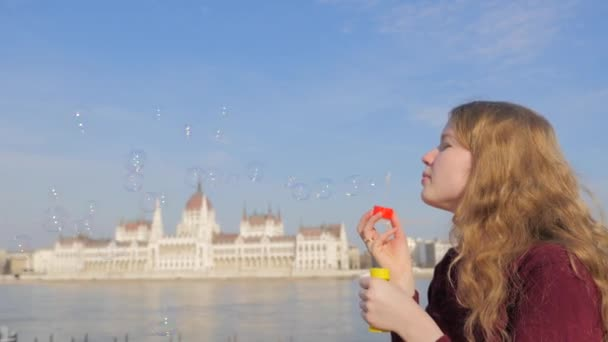 Attractive young woman blowing bubble in the Budapest