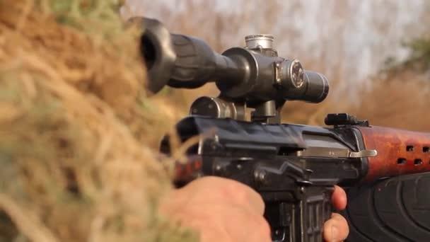 Egy mesterlövész lefekvés közben álcázott mesterlövész ruhában célba vett lövéseket ad le egy mesterlövészpuskából, optikai rálátással, közelről a puskáról, Full HD, hang nélkül..