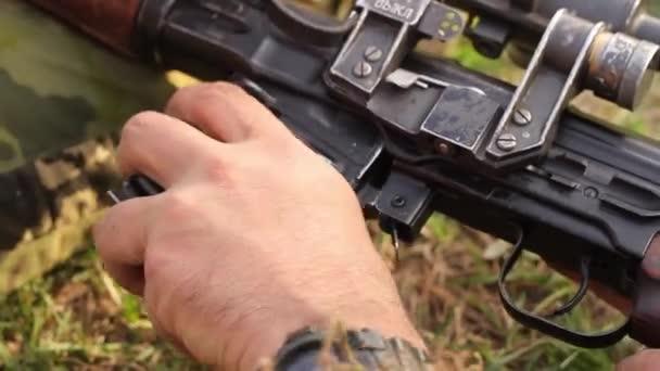 Közelkép egy férfi kézről, amint lőszert tartalmazó tárat helyeznek el egy mesterlövész puskában, optikai célzással. Egy orosz puska és optika. Teljes HD.