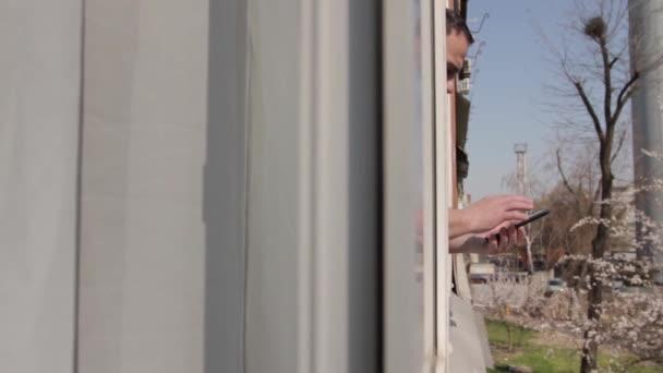 Ein Mann am offenen Fenster blättert in einem Smartphone, findet, was er sucht, trifft eine Wahl, lächelt fröhlich. Kamerabewegung durch den Fensterrahmen, von der Wohnung auf die Straße von links nach rechts. Medium Shot, Full HD, kein Ton.