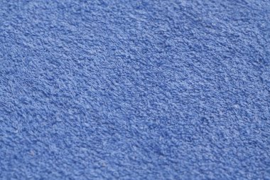 Blue color towel surface close-up with blur effect.