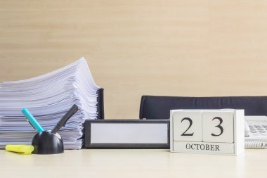 Closeup white wooden calendar with black 23 october word on blurred brown wood desk and wood wall textured background in office room view with copy space , selective focus at the calendar