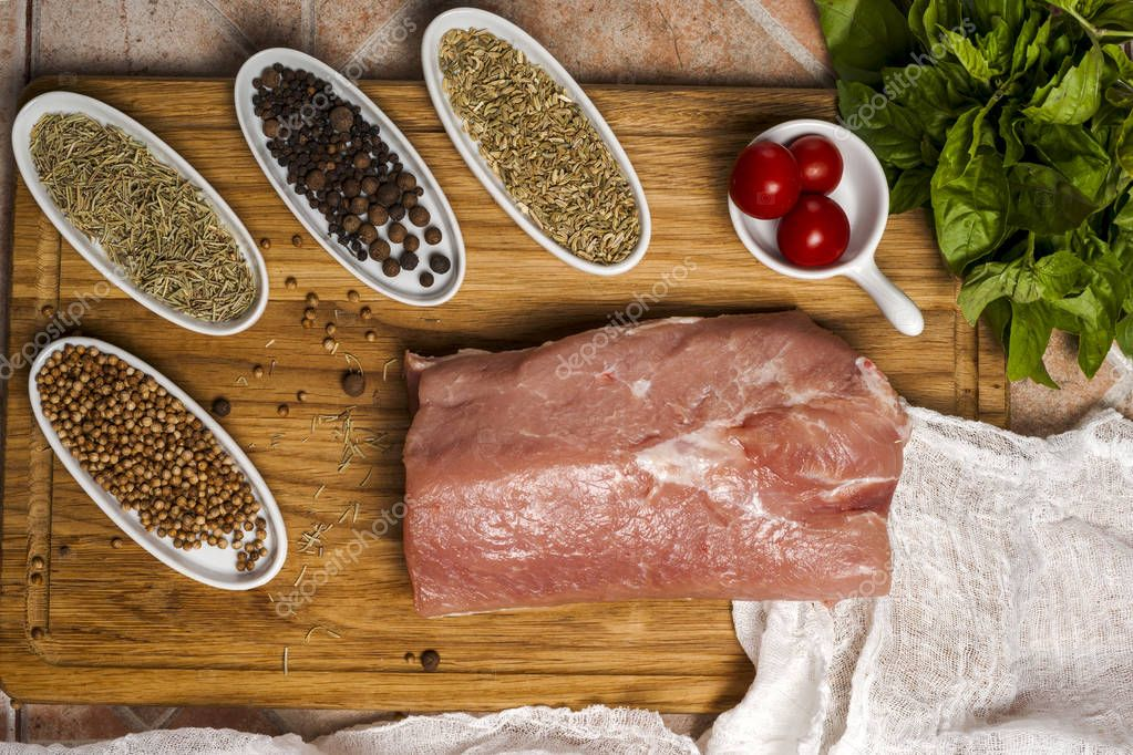 Fresh meat selection on wooden cutting board with spices in a white bowl