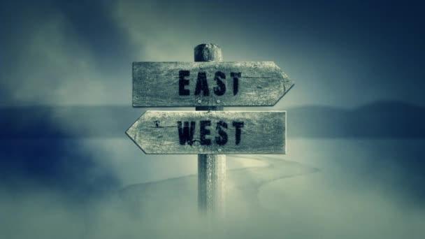 Stará dřevěná cedulka na středním Cross Road se slovy, východ nebo západ