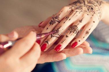 Applying mehndi on female hand