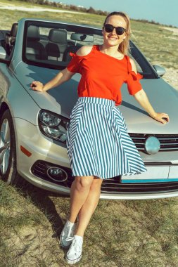 Attractive young woman with sunglasses posing leaning on convertible car during a sunny day