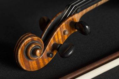 Old brown violin on black background