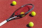 Tenisové míčky a raketa na travnaté hřiště