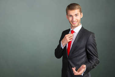 Portrait of young handsome businessman on grey background