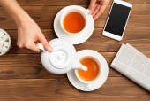 Female hands holding aromatic fresh tea on wooden table