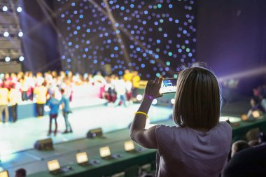 Girl with a smartphone taking photo of concert stage
