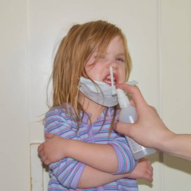 the child in a medical mask is sprayed with antiseptic from the virus