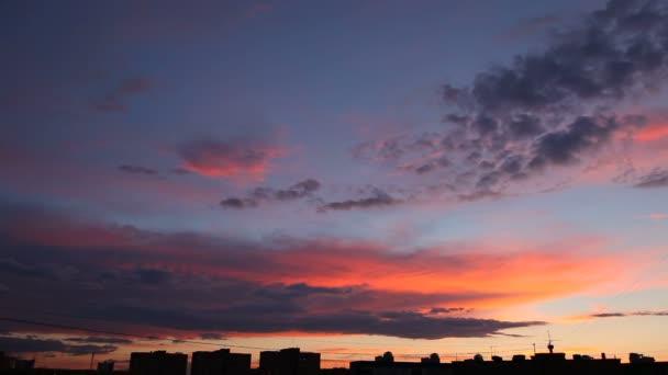 Čas zanikla klip načechraný mraky nad západu slunce na obloze. Večerní panoráma, silueta budov. Krásné cloudscape.