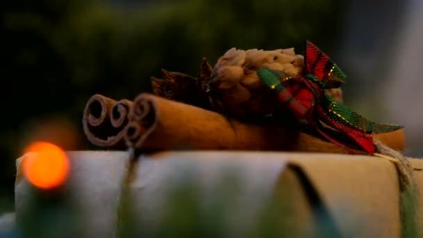Vánoce a nový rok na pozadí s dárky, osvětlení, svíčky a různé dekorace. Dárek do papíru řemeslo se skořicí