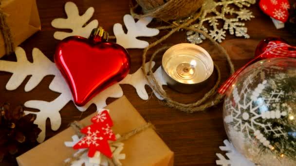 Vánoce a nový rok na pozadí s dárky, osvětlení, svíčky a různé dekorace. Dárek v kraftový papír s červená jedle.