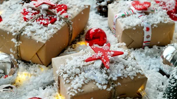 Karácsonyi és újévi háttér bemutatja, szalagok, labdák és más dekorációk a hó. Jelen csomagolva a vörös csillag kézműves papír.