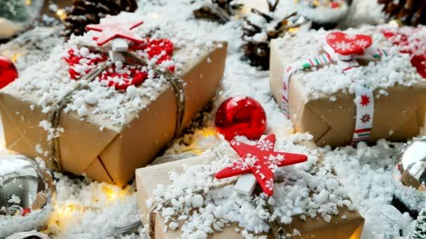 Vánoce a nový rok na pozadí s dárky, stuhy, plesy a různé dekorace na sněhu. Současnost v kraftový papír s červenou hvězdou.