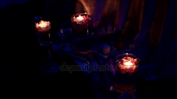 Element des Dekors - brennende Kerzen in Leuchtern mit Rosenblättern.