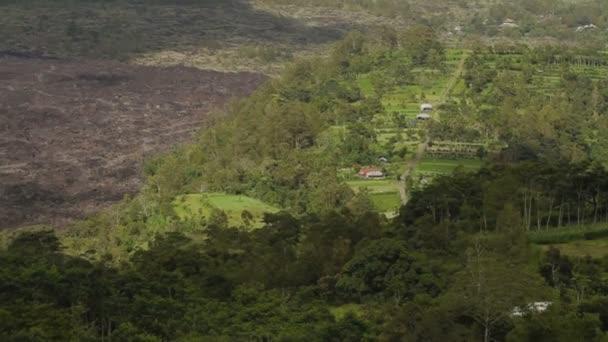 A Batur vulkán lábánál. A légi felvétel a Kintamani. Láva tájkép erdővel, téli esős évszak felhős nap. Bali Indonézia