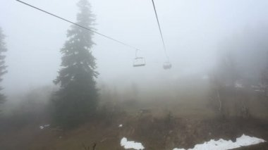 Tourists go in cabins on the ropeway through fog. Early morning trip above misty forest in Mestia, Georgia.