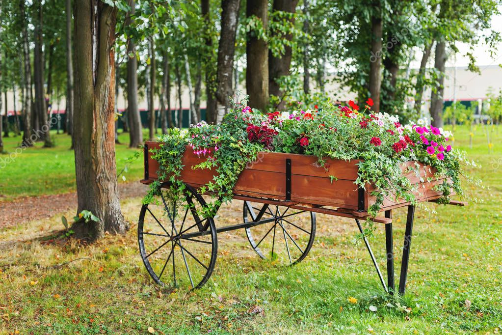 Parterre de fleurs en forme comme un chariot en bois Decoration parterre