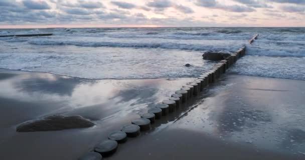 Wellenbrecher aus Lärchenstämmen. Stärkung der Küste, um den Sand am Strand zu halten. wunderschöner Sonnenuntergang in zelenogradsk, russland.