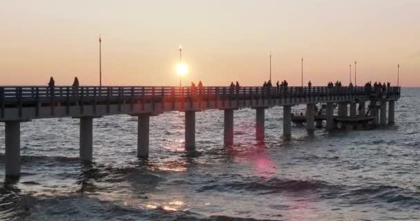 Silhouetten von Menschen, die auf der Seebrücke gegen den Sonnenuntergang gehen. Einheimische fischen, Touristen gehen vor dem Schlafengehen spazieren. zelenogradsk, Russland.