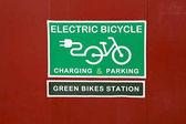 Fotografie Tisch Laden  Parken von Elektrofahrrädern und grüne Fahrradstation auf rotem Hintergrund