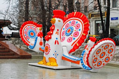 Traditional Dymkovo toy Cock as art object and swing at Russian national festival