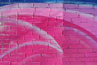 Colorful (pink, blue, white) painted brick wall as background, texture