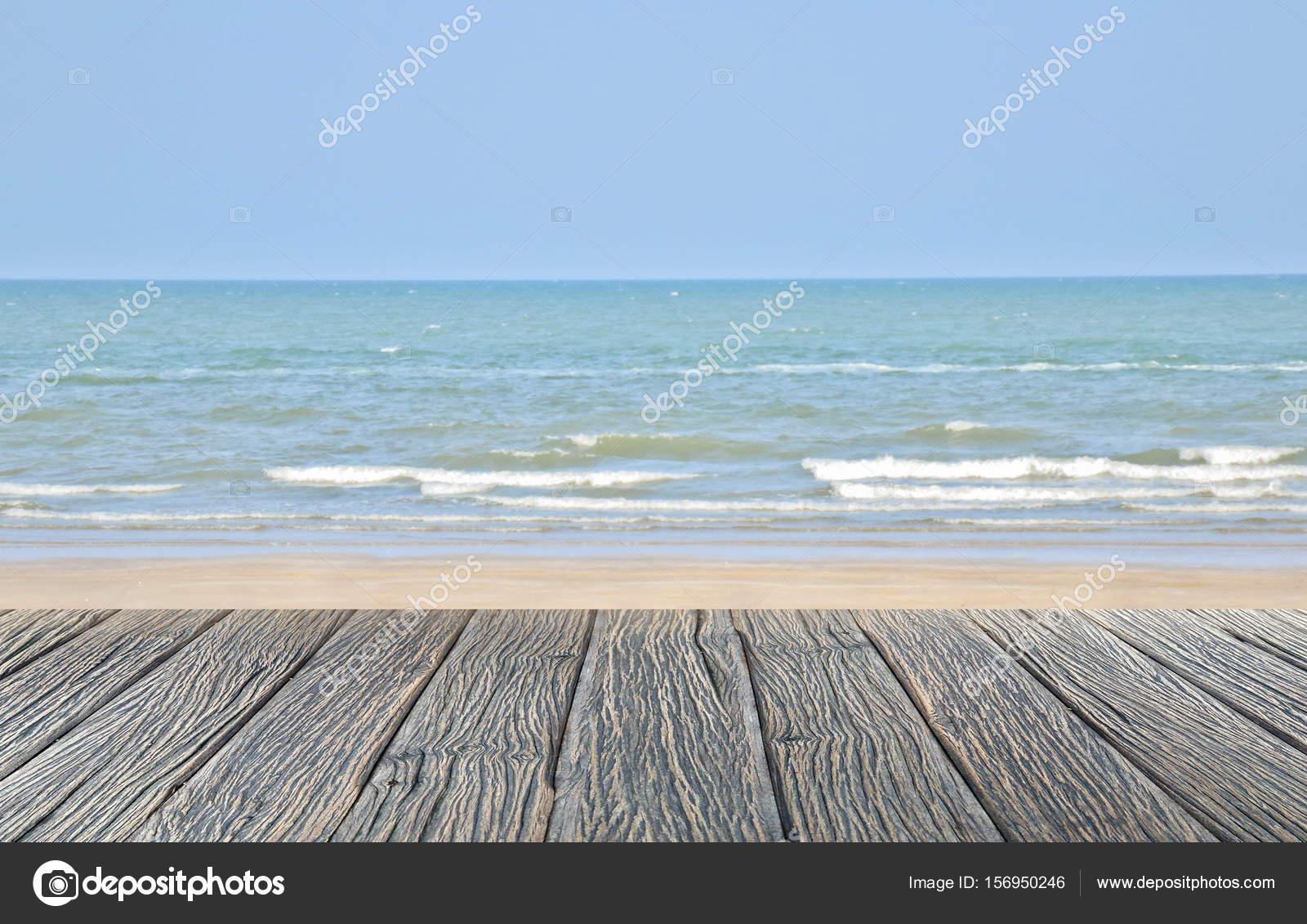 Houten vloer op zand strand en tropische zee met vervagen jetski