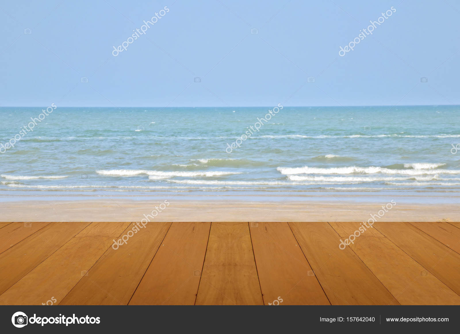 Houten vloer op zand strand met de zee en de blauwe hemel van