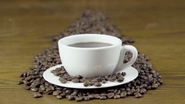 Detailní záběr na horké kávy v šálku na dřevěný stůl. Kouřící kávy s fazolemi a okolí