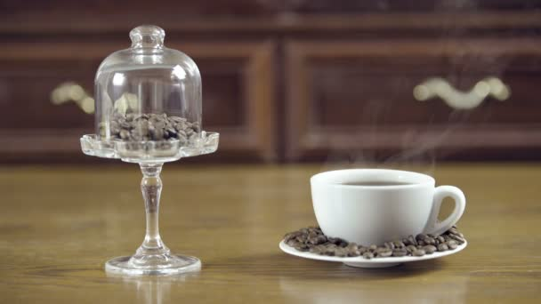 Coffee cup with beans on a decorative stand. Steaming cup of coffee. Beautiful glass stand.
