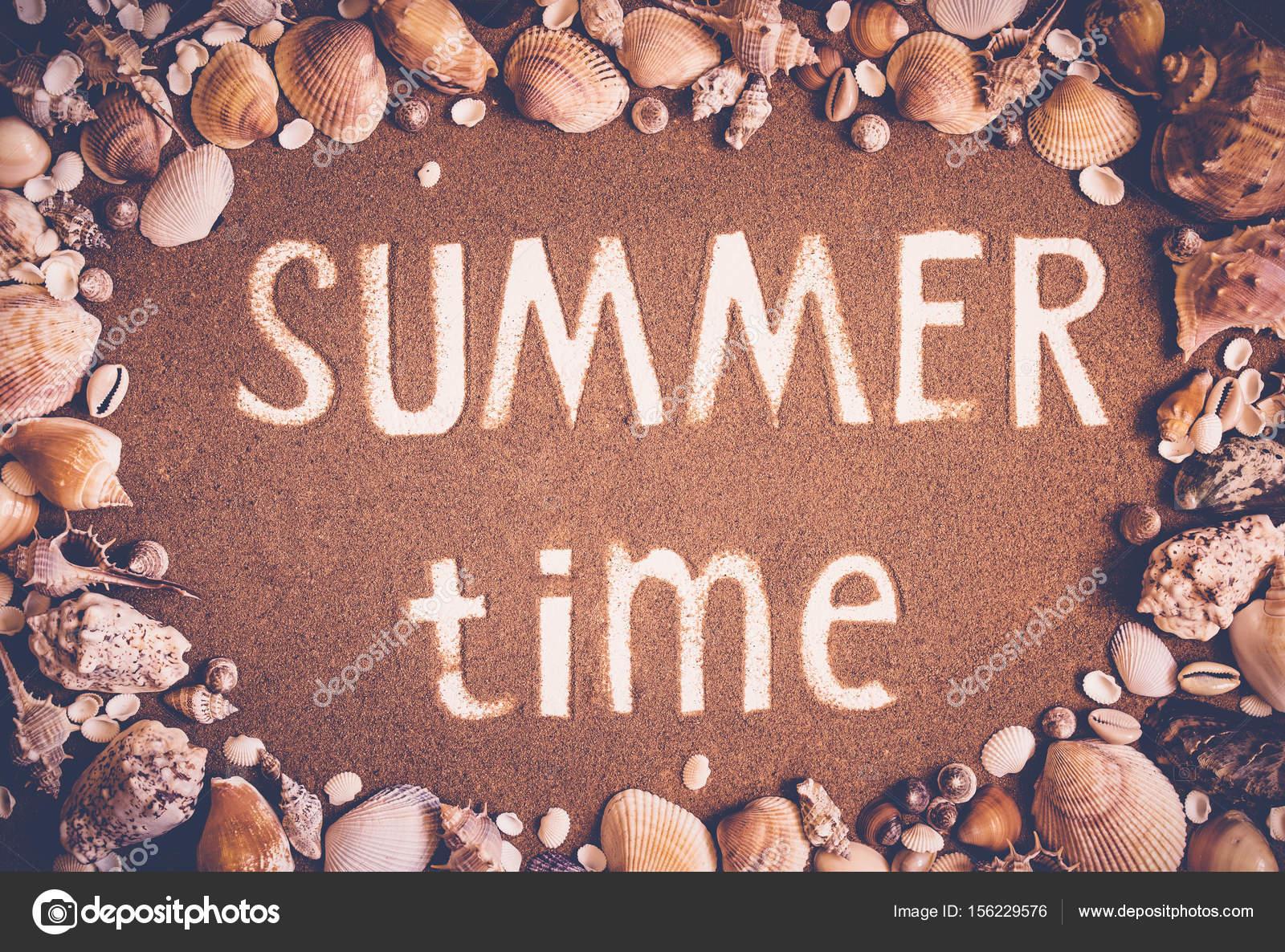 Horario de verano está escrito en la arena en el marco de las ...