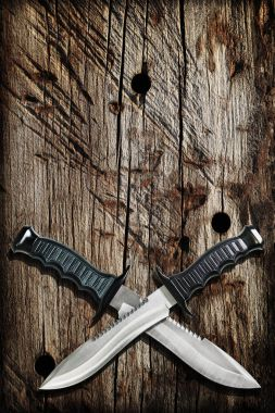 Tactical Combat Hunting Survival Bowie Knives With Crossed Blades On Grunge Vignetted Old Battered Grooved Wood Background