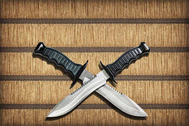 Two Crossed Blades Tactical Combat Hunting Survival Sawback Bowie Knives Set On Yellow Plaited Paper Parchment Place Mat Vignetted Grunge Texture